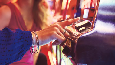 woman pushing button on slot machine